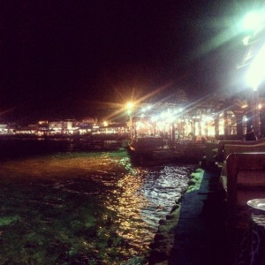 Dahab's restaurants seen at night from Sea House restaurant. It has tables overhanging the sea and the water is lit so you can see fish in it.